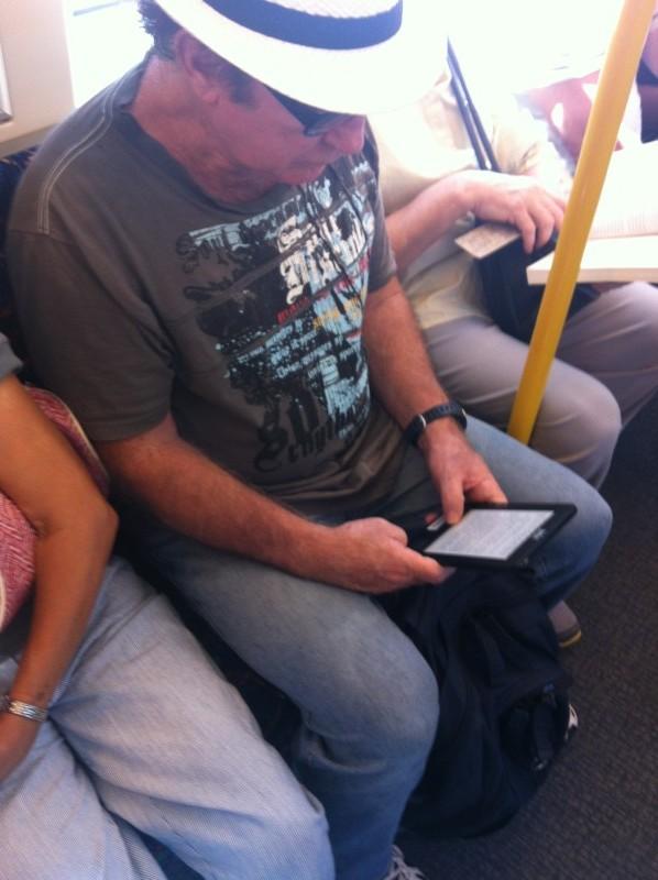 Pessoa lendo no kindle, no trem, em Perth