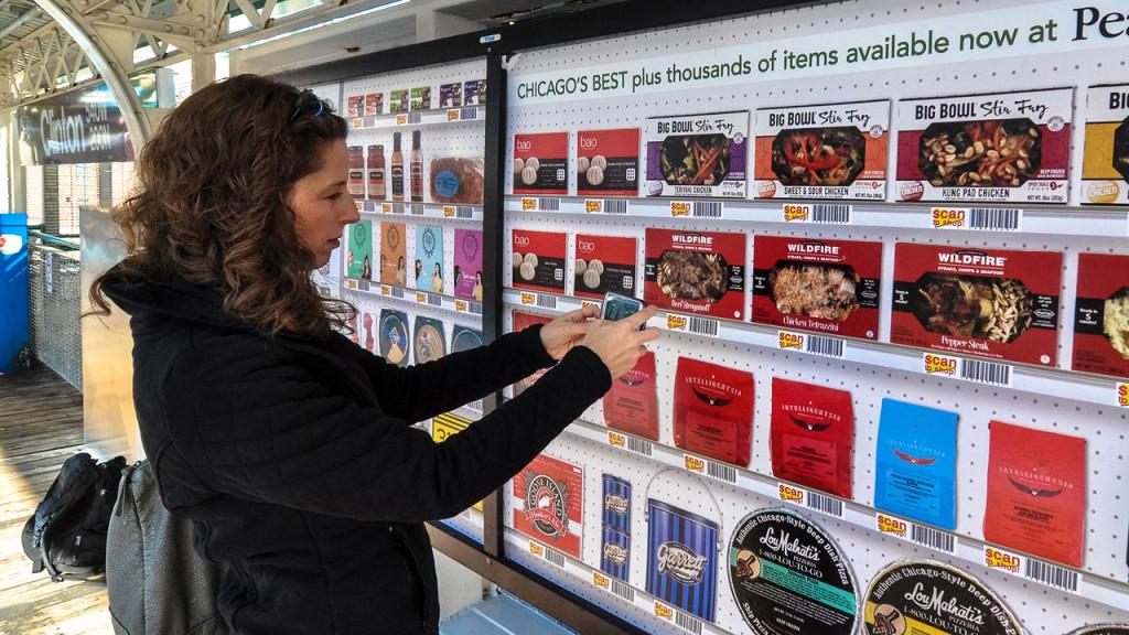 Mulher utiliza o celular pra fazer as compras da semana enquanto espera pelo metrô em Chicago