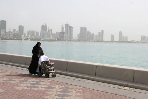 Mulher com roupa típica caminhando com bebê pelo corniche