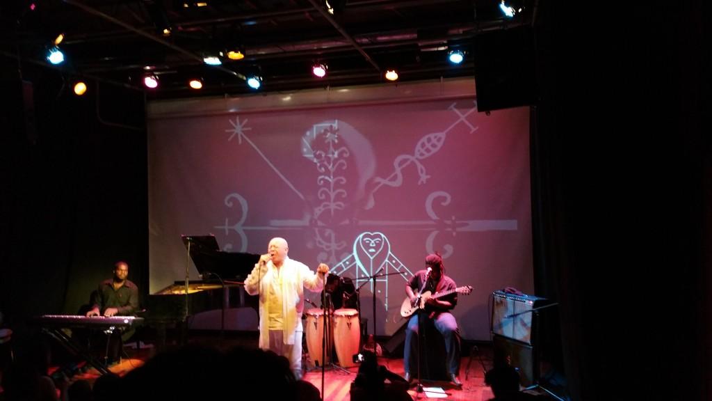 Durante uma apresentação musical do cantor James Germain, imagens relacionadas ao Voudou são projetadas na parede.