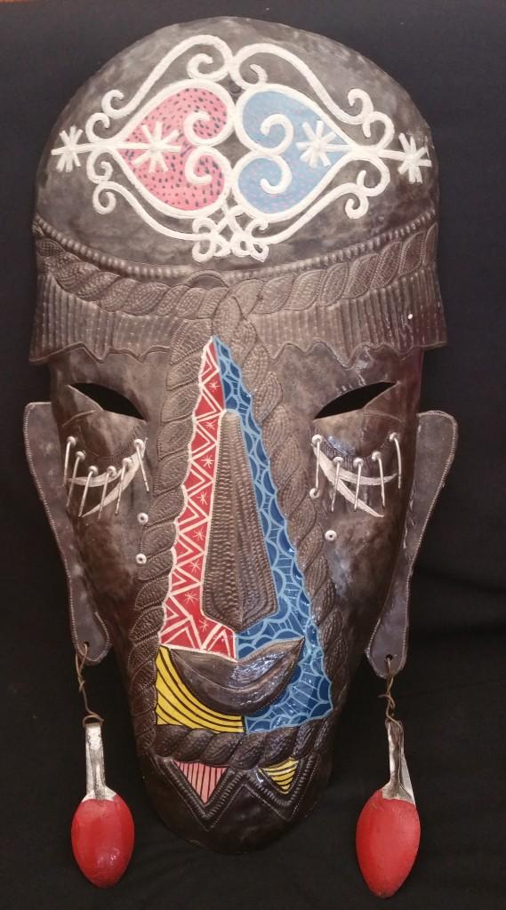 Escultura em metal com veve na fronte.