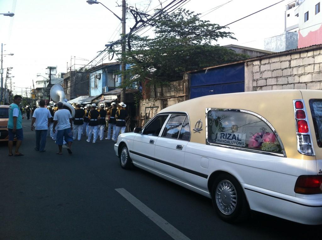 Carro fúnebre acompanhado pela banda é quem puxa o cortejo.