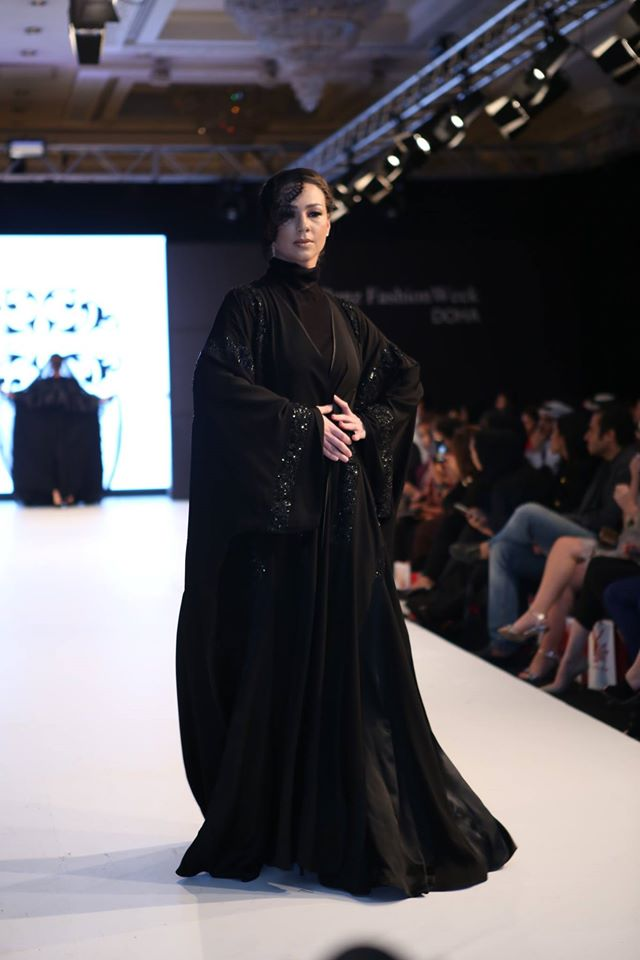 Desfilando com uma abaya (veste tradicional) e um pequeno véu de lado apenas simbólico. Como é um desfile de moda não caia bem o uso dos véus tradicionais.