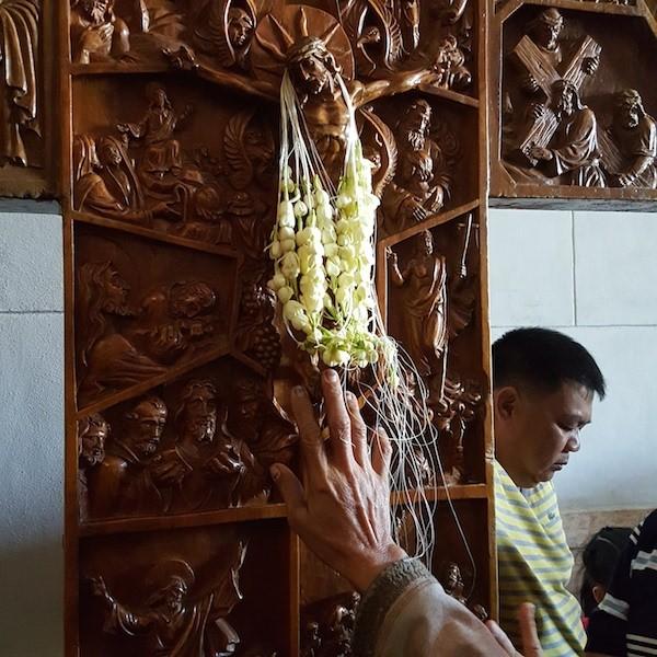 Colar de sampaguita, a flor típica filipina, é depositado sobre a cruz