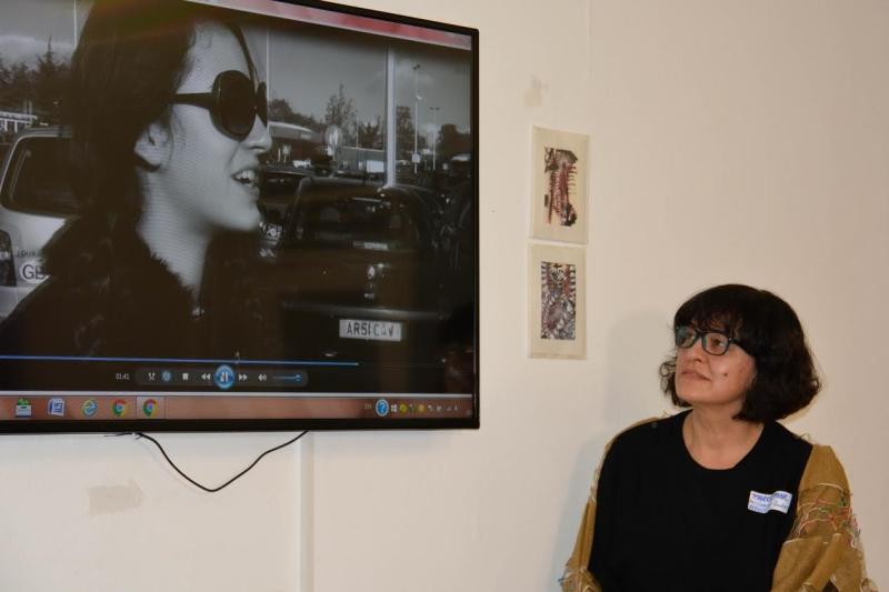 A artista Márcia Mar apresentando um vídeo da artista Regina Mester