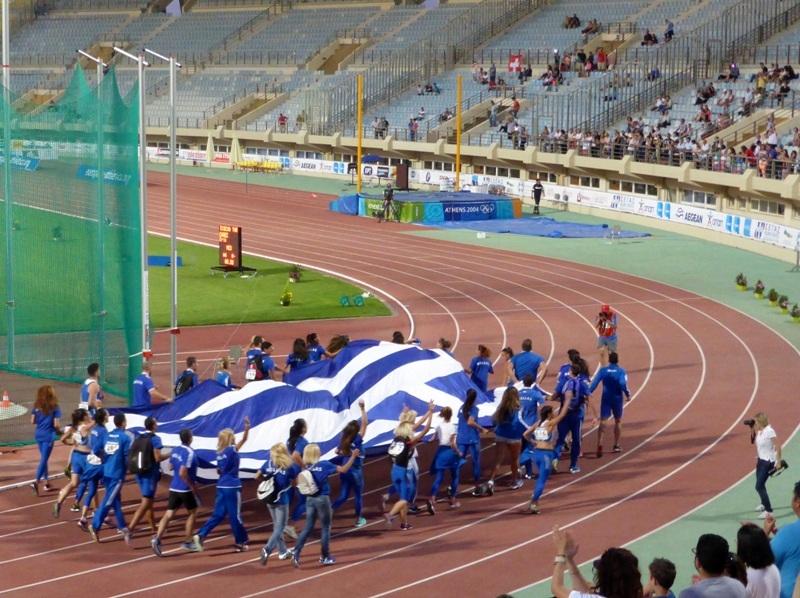 Atletas carregando a bandeira da Grécia, no Campeonato Europeu de Atletismo, em Heraklion