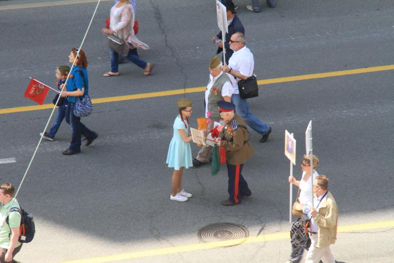 Menina entrega flores a veterano de guerra no meio do Regimento Imortal