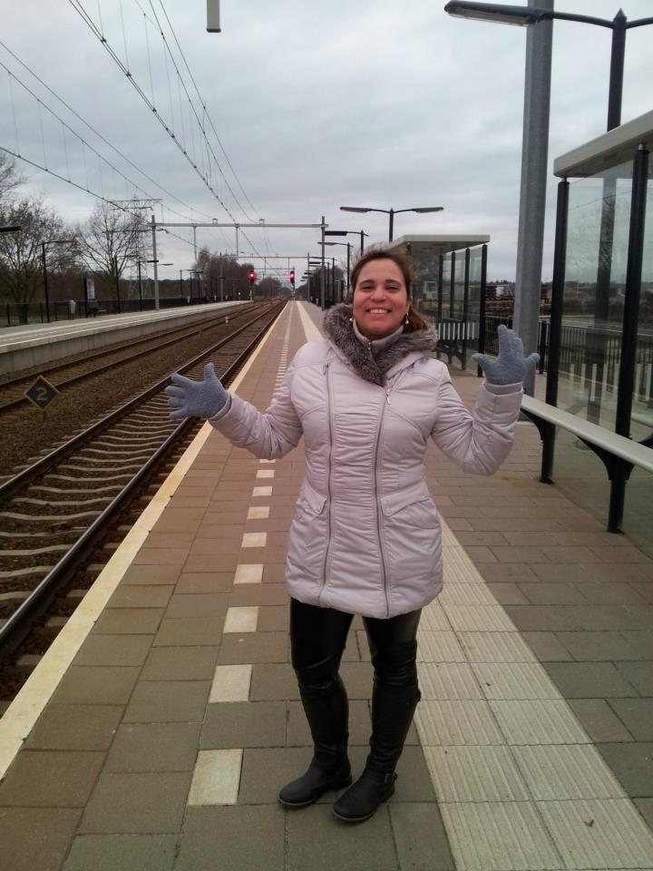 Na rua, esperando o trem, luvas e casaco com capuz, não precisou de lenço pois o casaco fechava até em cima no pescoço e era justinho.